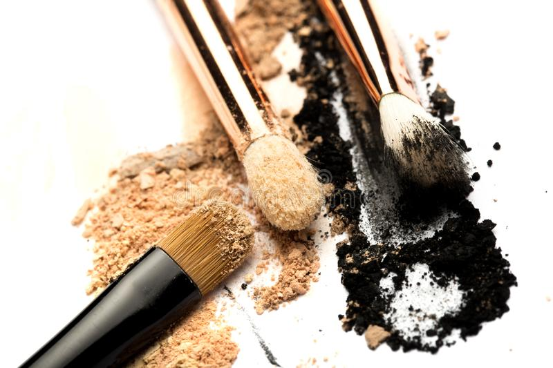 Close-up side view of professional make-up brush with natural bristle and black ferrule with crashed eyeshadow isolated on white stock image