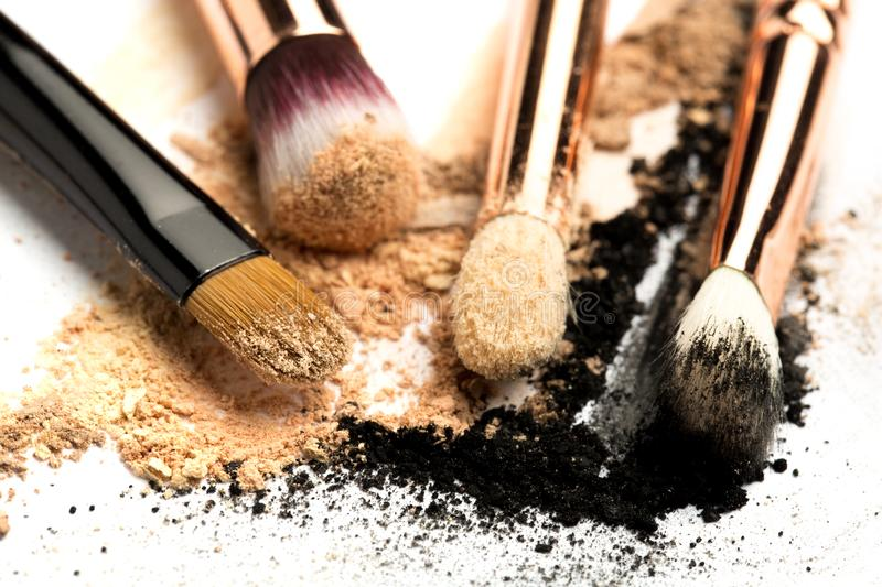Close-up side view of professional make-up brush with natural bristle and black ferrule with crashed eyeshadow on white royalty free stock image