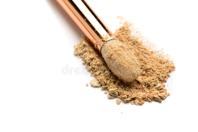 Close-up side view of professional make-up brush with natural bristle and black ferrule with crashed eyeshadow on white stock photos
