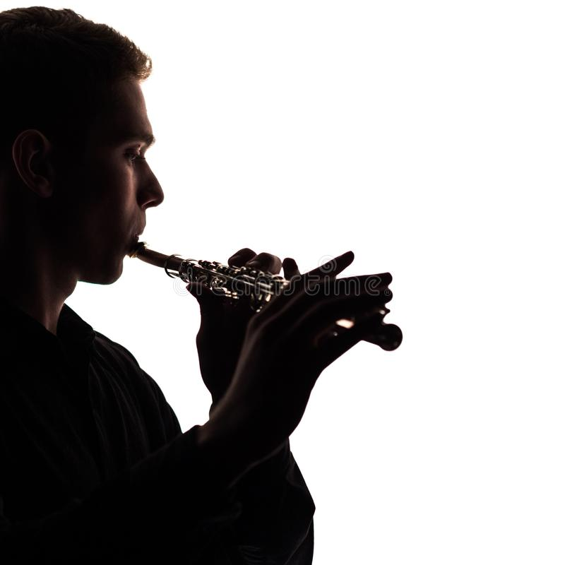 A close-up of the silhouette of a flute in the hands and on the lips of a musician. The guy gives out sounds to a white stock photo