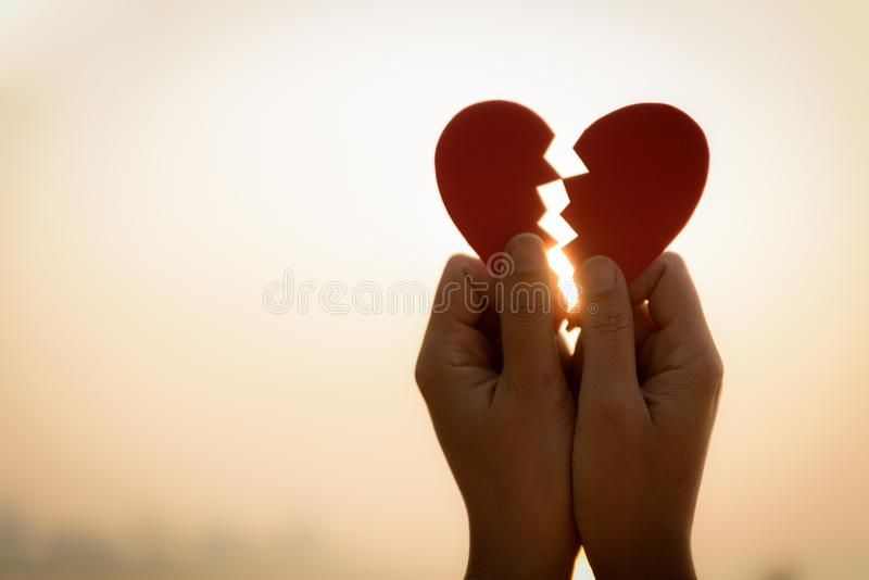 Close up and Silhouette of Woman hand holding broken paper red heart royalty free stock image