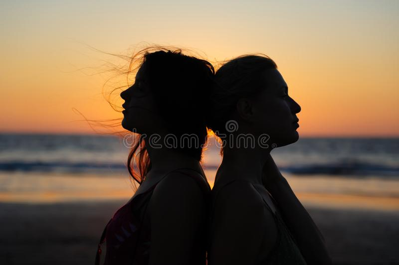 Close up silhouette of womens couple in romantic scene of sunset over the sea. Beautiful female young lesbian couple in love.  royalty free stock photo
