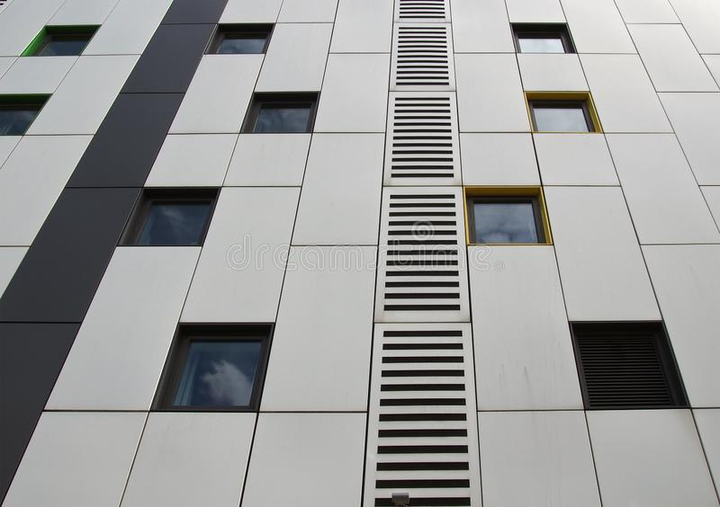 Silver colored metal cladding panels on a modern building with repeating windows and geometric grid design. Close up of silver colored metal cladding panels on a stock image