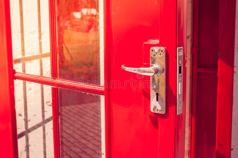 Close up silver metal door handle on opened red modern door of phone booth. Selective focus stock photography