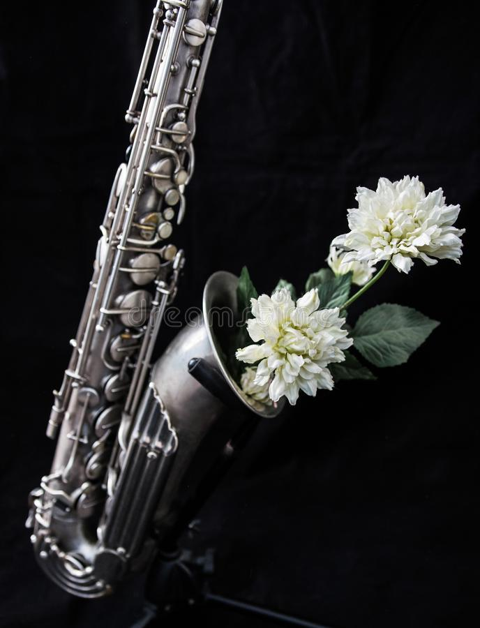 Close up of a silver saxophone decorated with white flowers royalty free stock images