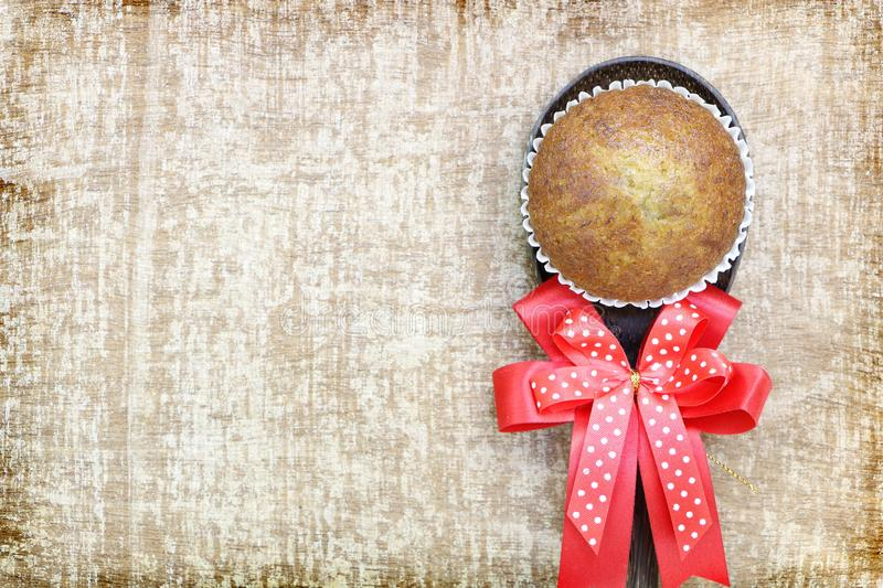 Close up single banana cup cake bakery top view on wood ladle with big red bow look delicious on wooden table background stock images
