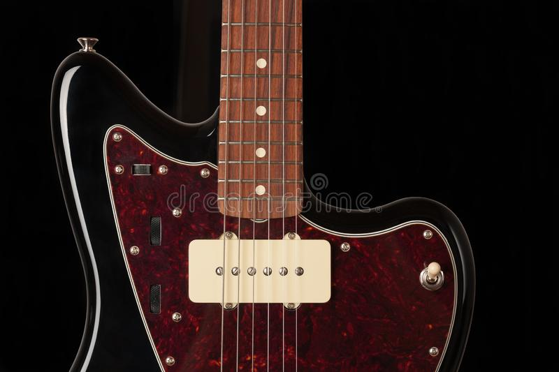 Close up of single coil and controls and  3 way pickup switch on black electric guitar. Studio shoot. Red tortoise shell pickguard, alder body, maple neck royalty free stock photo
