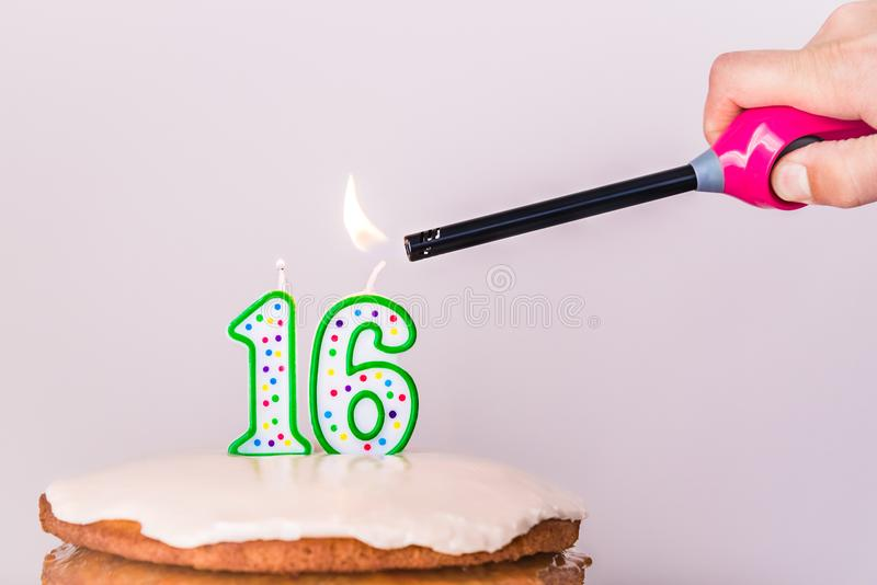 Man`s hand lighting sixteenth birthday candles on rustic vanilla layer cake. Close up of sixteenth birthday candles on a layered vanilla cake, being lit with a royalty free stock photography