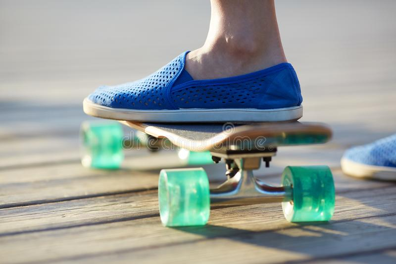 Close up of skateboard, urban lifestyle. Close up of skateboarders feet in sneakers on skateboard, urban lifestyle royalty free stock images