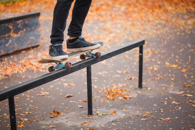 Close-up of a skateboarder`s foot in an autumn skate park. A skateboarder makes a trick. The concept of sport stock image