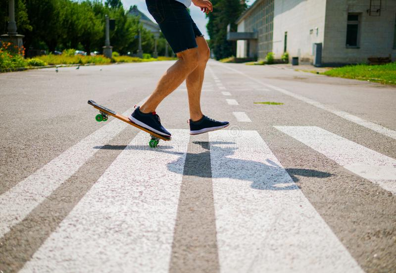 Close-up of skateboarders feet while skating in skate park. Man riding on skateboard. stock images