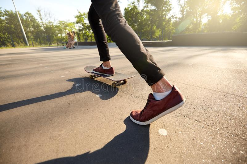 Close-up of skateboarders feet while skating in skate park. Man riding on skateboard. view, low angle shot. royalty free stock images