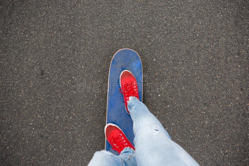 Skateboarders feet while skating through the street royalty free stock photo