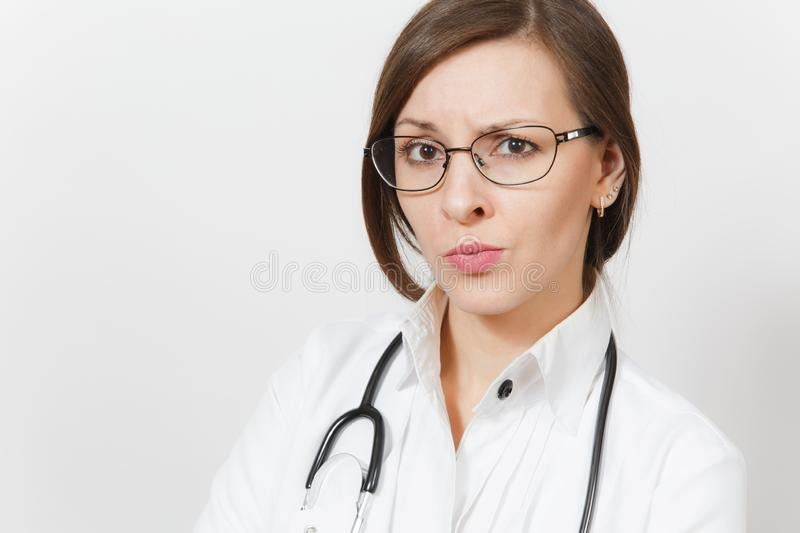 Close up skeptical sad brunette beautiful young doctor woman with stethoscope, glasses isolated on white background. Female doctor in medical gown. Healthcare royalty free stock photography