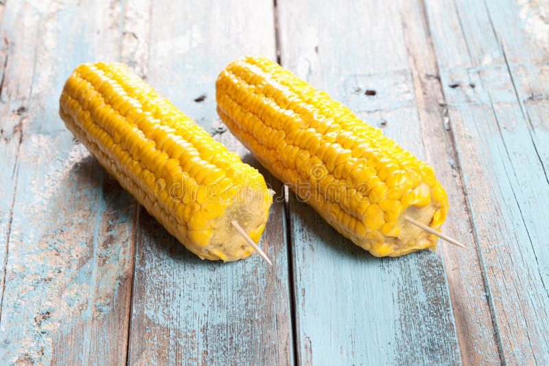 Close up of skewered corn cob on wooden table royalty free stock photography