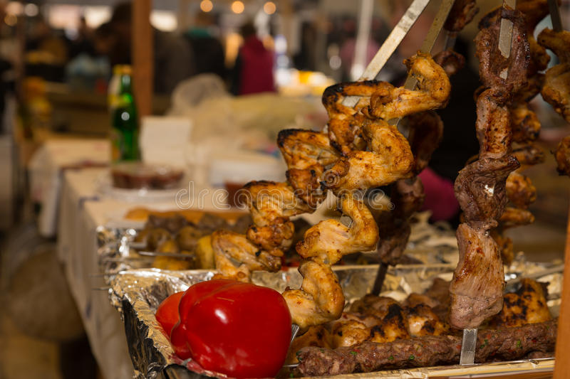 Close up of skewered meat kabobs in tin tray. On long table besides other foods at a party stock images