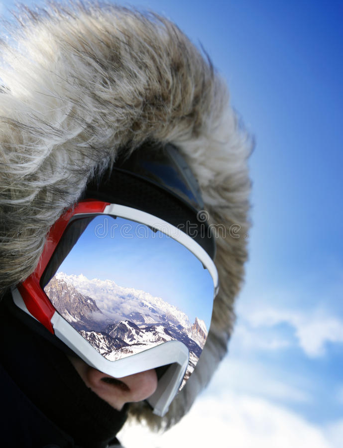Close up of the ski goggles. Of a man with the reflection of snowed mountains