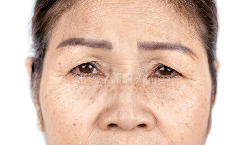 Close up skin wrinkle and freckles of old asian woman face stock photography