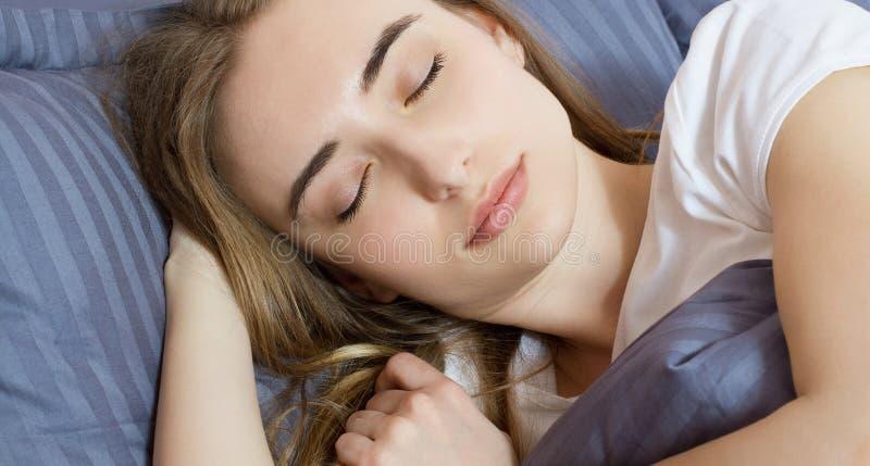Close-up - Slaap Jonge vrouwenslaap in bed Portret die van Mooi Wijfje op Comfortabel Bed met Hoofdkussens in binnen het Vastzett stock afbeeldingen