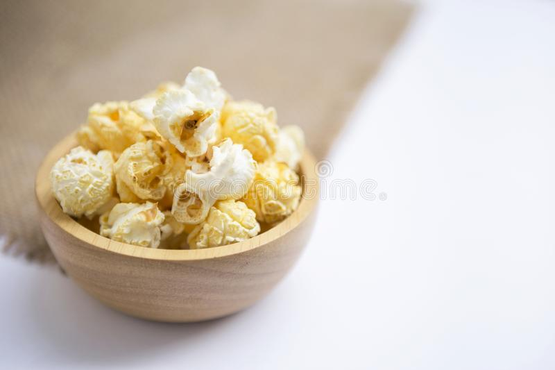 Close-up slated popcorn in ronde houten kom op witte achtergrond royalty-vrije stock fotografie