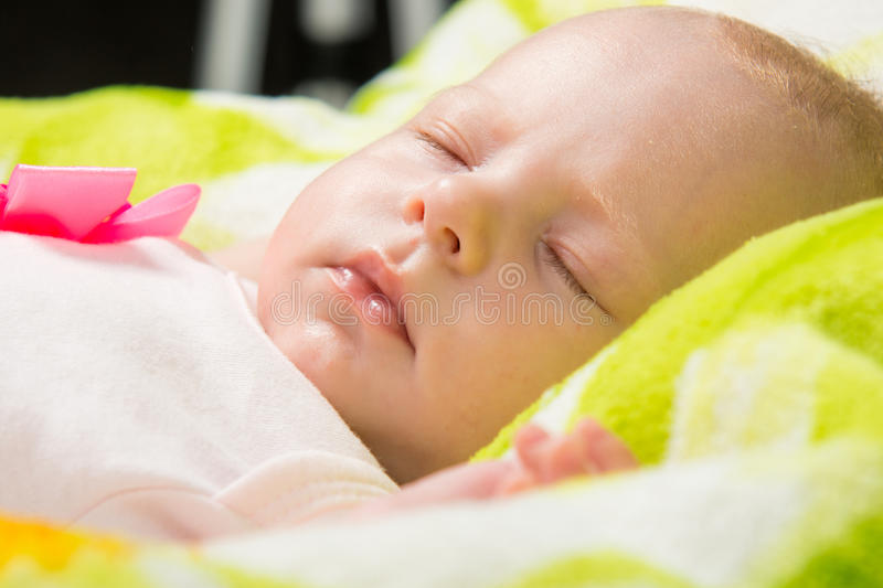 Close-up of a sleeping baby in the crib. A two-month baby girl Europeans lies on a soft bed on colored coverlet stock photography