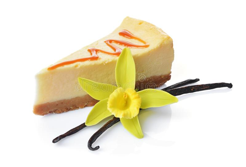 Close-up slice of delicious homemade cheesecake with caramel sauce, vanilla pods and flower. Isolated on white background stock image