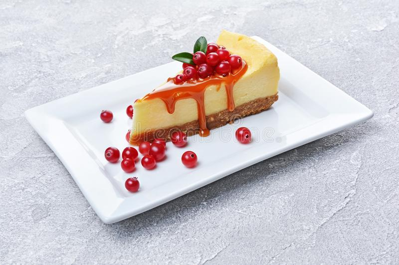 Close-up slice of delicious homemade cheesecake with fresh cranberries and caramel sauce on gray concrete. Close-up slice of delicious homemade cheesecake with stock images