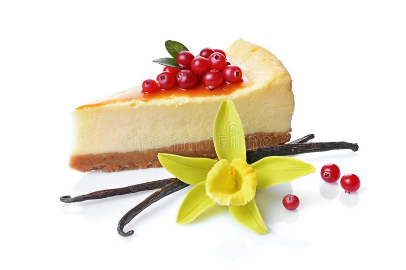 Close-up slice of delicious homemade cheesecake with fresh cranberries, caramel sauce, vanilla pods and flower. Isolated on white background stock photo
