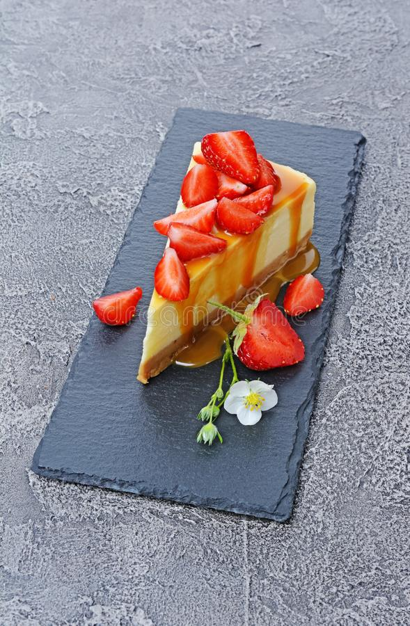 Close-up slice of delicious homemade cheesecake with fresh strawberries, spring flowers and caramel sauce on black slate board. On gray concrete background royalty free stock photography