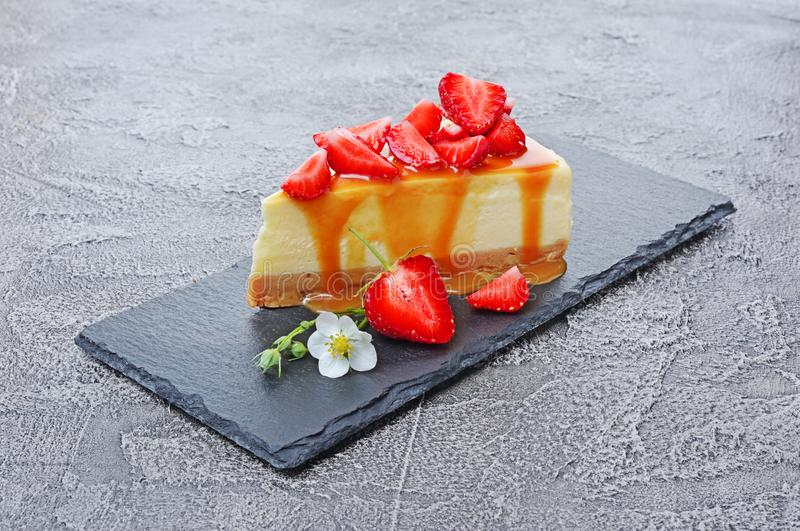 Close-up slice of delicious homemade cheesecake with fresh strawberries, spring flowers and caramel sauce on black slate board. On gray concrete background royalty free stock image