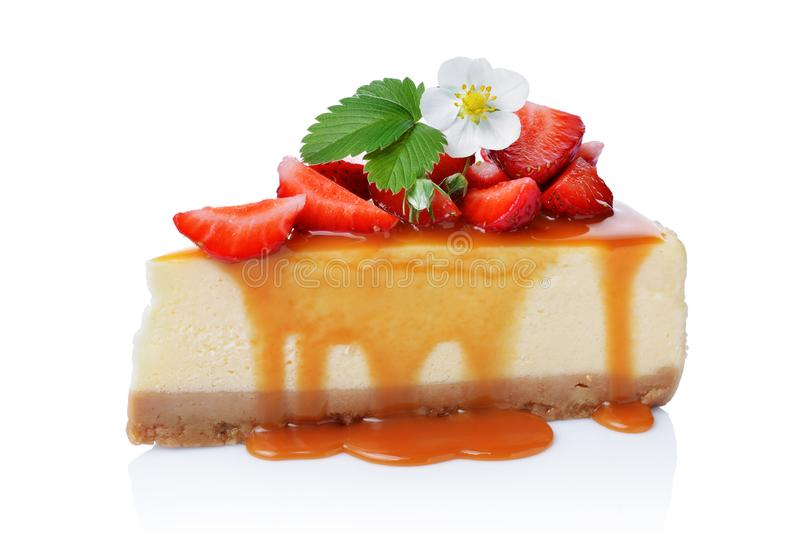 Close-up slice of delicious homemade cheesecake with fresh strawberries, spring flowers and caramel sauce. Isolated on white background royalty free stock images