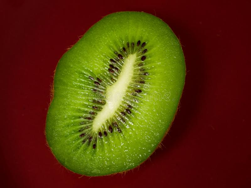 Close up of a slice of a kiwi fruit placed over a red Surface stock photography