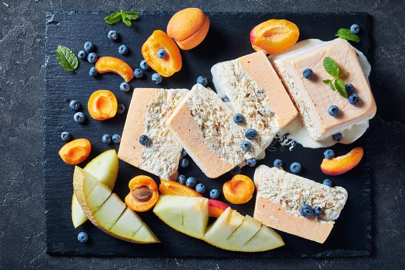 Close-up of sliced almond apricot sweet Semifreddo. Close-up of melting Semifreddo alle Mandorle, Sicilian Almond apricot melon Semifreddo served on a slate royalty free stock image
