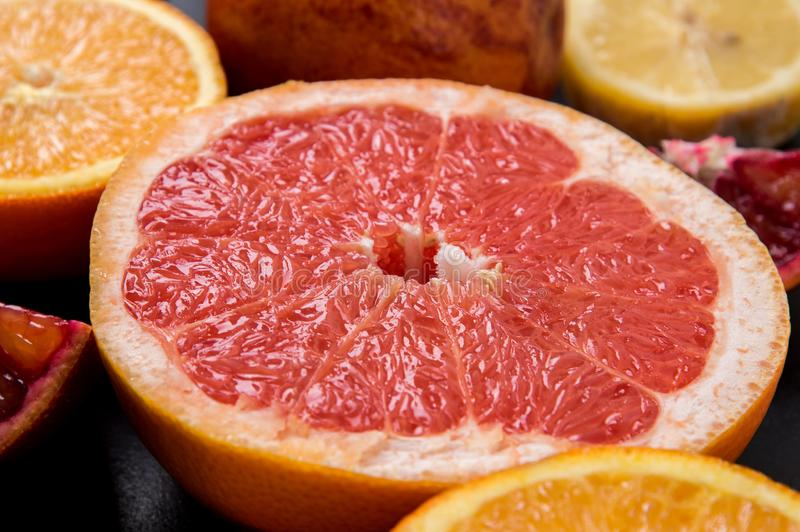 Close up. Sliced in half juicy grapefruit on a black background royalty free stock photos