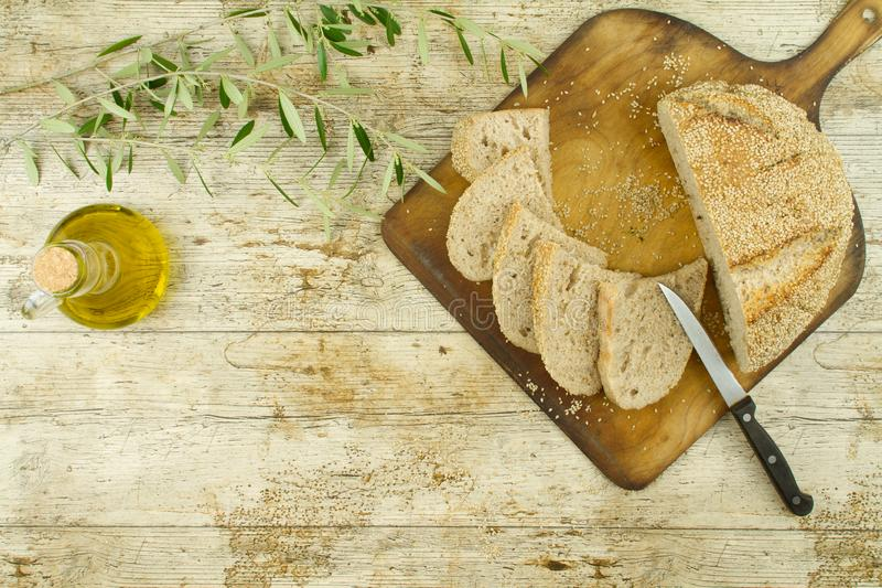 Close-up of a sliced loaf of homemade bread with sesame seeds, ampoule of extra virgin olive oil and an olive branch on wooden stock photo