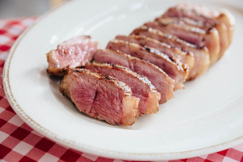Close up Sliced medium rare charcoal grilled boneless wagyu Top Loin steak in white plate on red and white pattern tablecloth.  royalty free stock photography