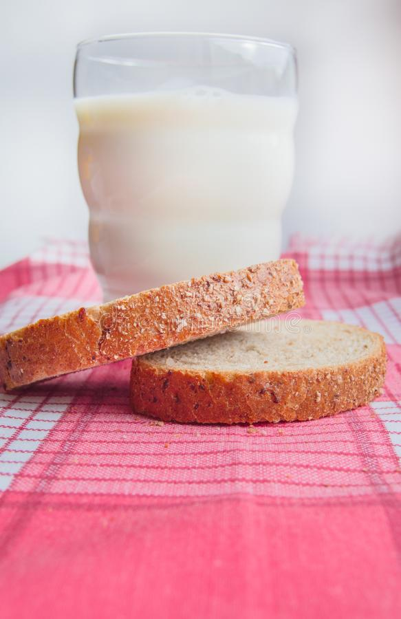 Close-up of Sliced rye bread and a glass of milk on a cloth red napkin, rustic background, healthy food, vertical shot royalty free stock images