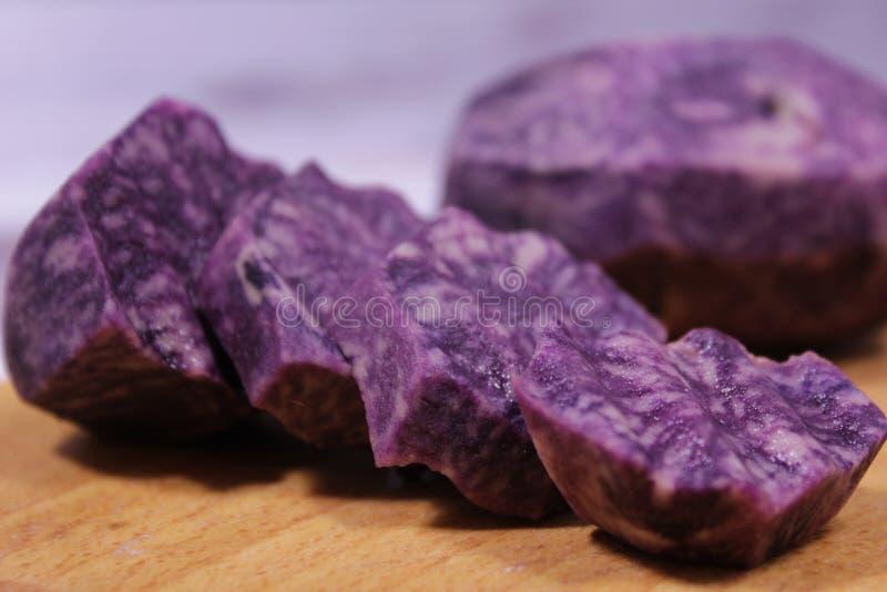 Close-up on sliced wavy circles of purple potatoes. Decorative food design. Decorative food design royalty free stock photography