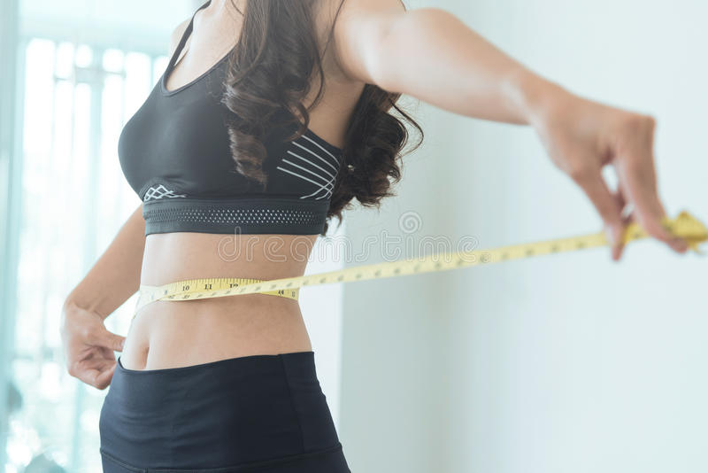 Close up of Slim Asian woman waist with measuring tape. copy spa royalty free stock photography
