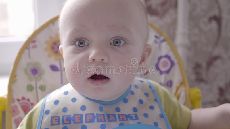 Beautiful little toddler boy sitting at the kids table in the blue bib, watching into the camera and babbling close up. Close up slo motion video of a beautiful royalty free stock image