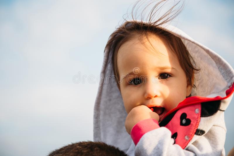 Close up of small baby girl in grey hood sitting on father`s shoulders on the sky background royalty free stock images