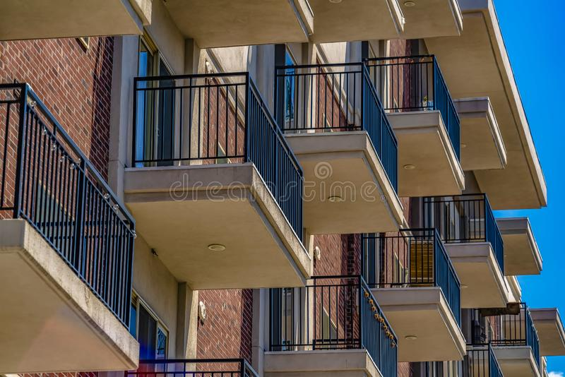 Close up of the small balconies of a residential building on a sunny day stock images