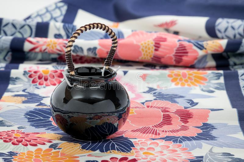 Small Japanese pot on a printed cloth royalty free stock images