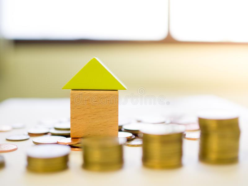 Close up small blocks house with stack of coins stock photo