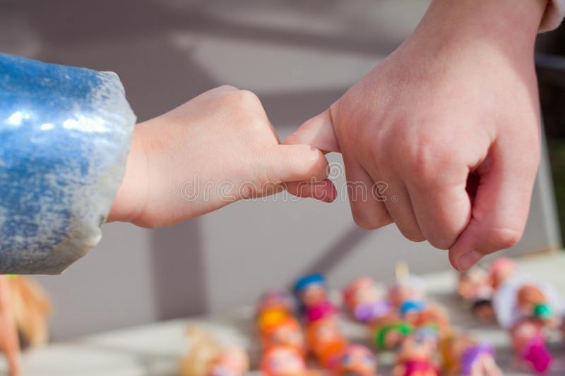 Close up of small kids reconcile after fight making pinky promise, children make peace with hand gesture joining pinkies swear not. To argue or quarrel royalty free stock photos
