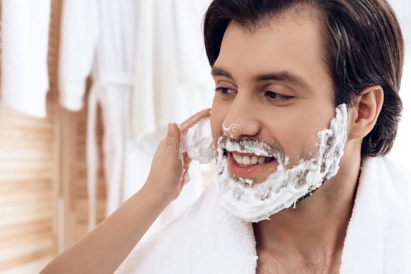 Close up. Small son smears father`s face with shaving foam. stock photo