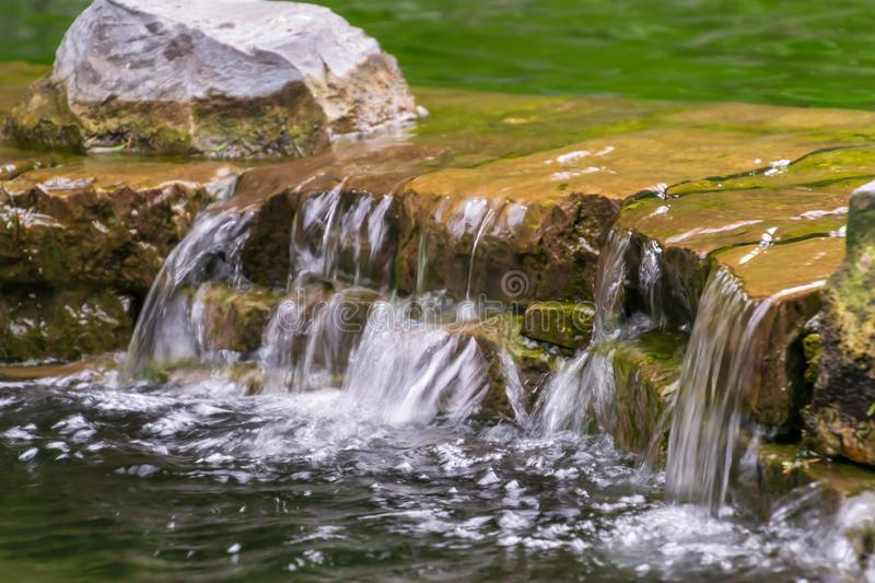 Close-up of small waterfall running over rocks with autumn leaves royalty free stock photos