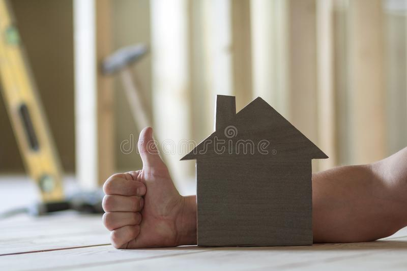 Close-up of small wooden model house on background of man`s hand with thumb-up gesture and blurred images of building tools. Inve. Stments in real estate stock photos