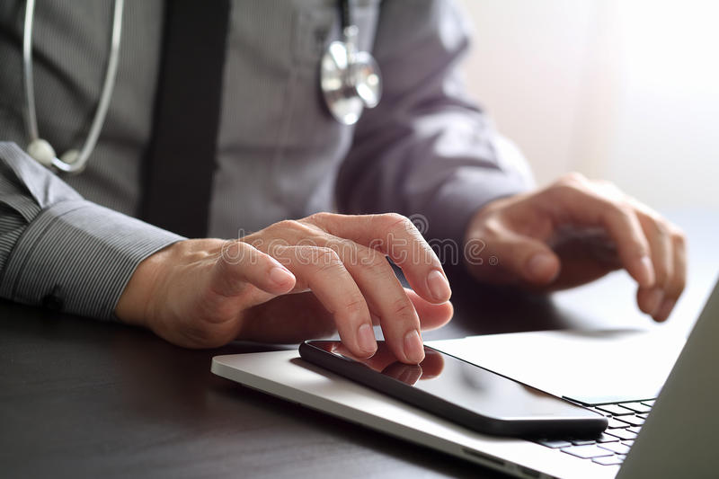 Close up of smart medical doctor working with mobile phone and l. Aptop computer and stethoscope on dark wooden desk stock photography