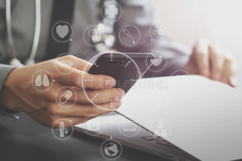 Close up of smart medical doctor working with mobile phone and l. Aptop computer and stethoscope on dark wooden desk with virtual reality icon diagram royalty free stock photography
